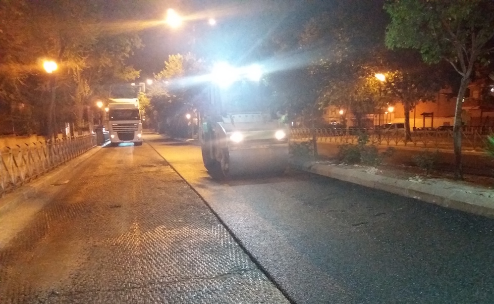 Asfalto con polvo de cucho de neumáticos reciclados en calle de Coslada, máquina asfaltando